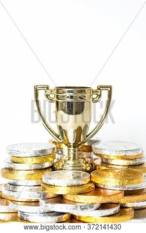 A Success Or Victory Concept With A Gold Trophy Or Cup Surrounded By Gold And Silver Coins In The Fo