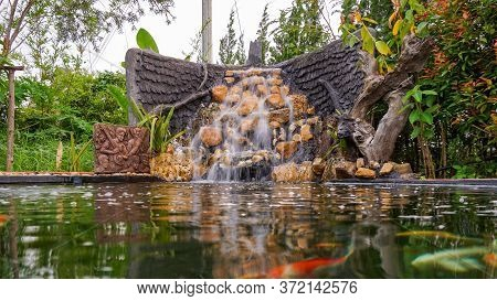 Fish Pond With Waterfall Fountain. Garden Waterfall Landscaping With Fishes, Rocks, Flowers And Plan