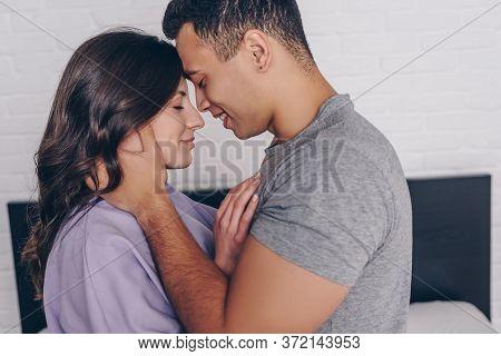 View Of Bi-racial Man Hugging Cheerful Girl With Closed Eyes