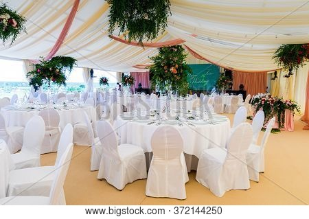 Banquet Hall With Flowers And Table Setting For A Reception Before A Large Reception