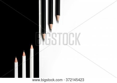 Composition With Black Pencils On A White Background And White Pencils On A Black Background Lying N