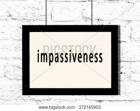 Black Wooden Frame With Inscription Impassiveness Hanging On White Brick Wall
