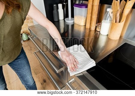 View Of Woman Cleaning Kitchen Worktop With Towel