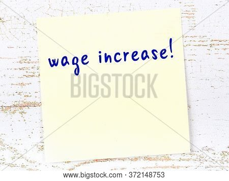 Concept Of Reminder About Wage Increase. Yellow Sticky Sheet Of Paper On Wooden Wall With Inscriptio