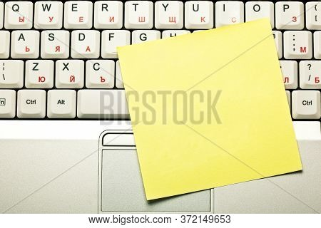 Top View Of A Blank Empty Clear Yellow Sticky Note On Grey Laptop Keyboard Trackpad.