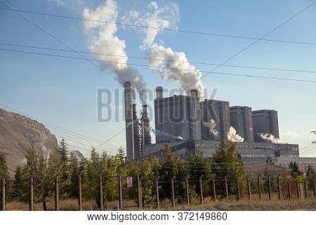 Industrial Smoke From Chimney On Blue Sky. Smoke Coming Out Of Factory Chimneys.