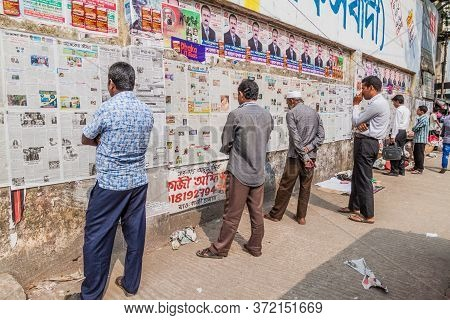Dhaka, Bangladesh - November 20, 2016: People Are Reading Daily Newspaper Published On A Wall In Dha