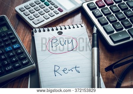 buy or rent question  on note with calculators on desk.