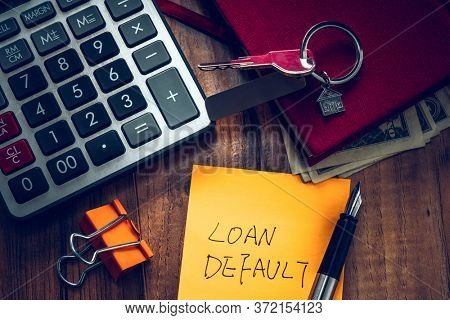 loan default word on note with us dollars and stuff on  desk.
