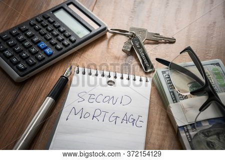 second mortgage word on note with us dollars and stuff on  desk.
