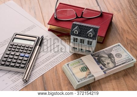 house model with mortgage agreemen on desk.