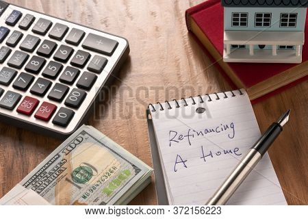 refinancing words on notebook with us dollars and stuff on wooden desk.