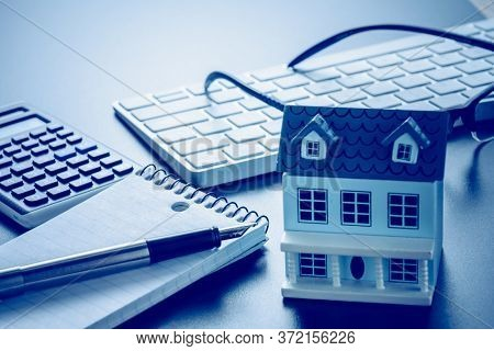 Miniature House and us dollars on keyboard