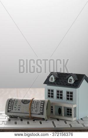 Miniature House on us dollars on desk.