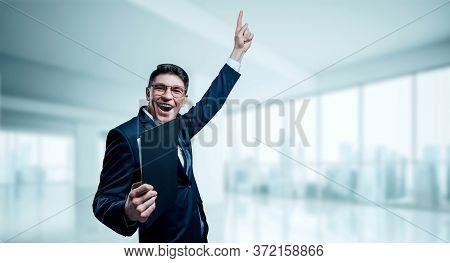 Man With A Tablet In His Hand Screams With Joy In The Office. The Concept Of Achieving Success In Bu