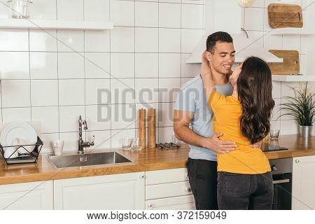 Young Woman Hugging Bi-racial Boyfriend In White Kitchen