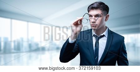 Portrait Of A Businessman In A Skyscraper Office. He Fix His Glasses With A Serious Expression On Hi