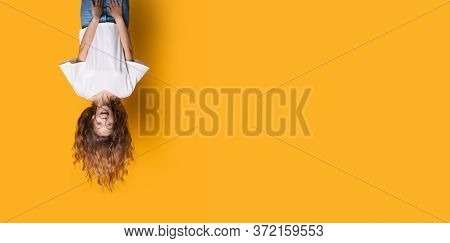 Upside Down Photo Of A Caucasian Woman In White Shirt And Jeans Smiling On A Yellow Studio Wall With