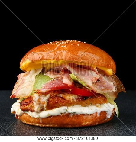 Tasty Burger With Chicken On Dark Isolated Background. Homemade Hamburger Or Burger With Fresh Veget