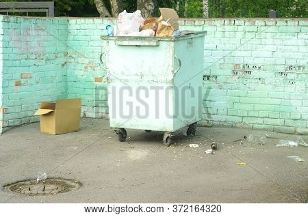 A Dumpster With Overflowing Garbage And An Empty Box In A Fenced Waste Storage Area.garbage Collecti