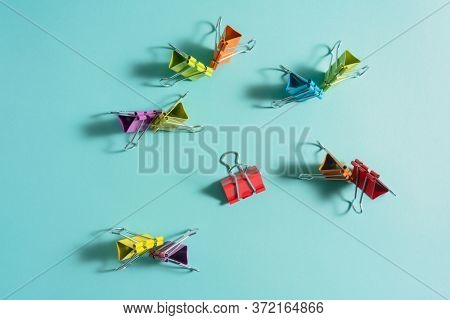 Multicolored paper clips on blue background.