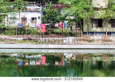 Puthia, Bangladesh - November 10, 2016: Laundry On The Banks Of Gopal Chowki Pond In Puthia Village,