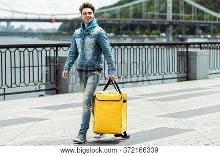 Courier With Thermo Bag Walking On Promenade
