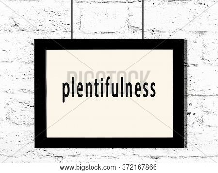 Black Wooden Frame With Inscription Plentifulness Hanging On White Brick Wall