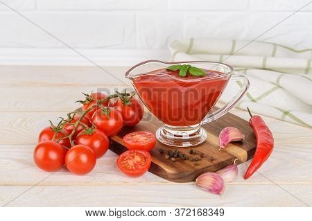 Tasty Thick Tomato Ketchup In A Glass Gravy Boat And Ripe Red Cherry Tomatoes, Garlic And Hot Pepper