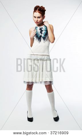 Beautiful asian fashion model female in vernal clothes posing over white background poster