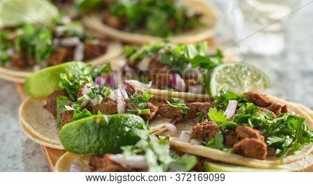 wooden tray with carne asada tacos on corn tortilla