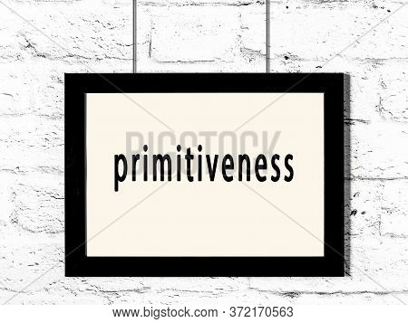 Black Wooden Frame With Inscription Primitiveness Hanging On White Brick Wall