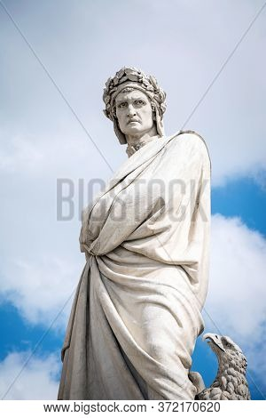 Statue Of Dante Alighieri In Piazza Di Santa Croce With Cloudy Sky Background. Florence, Italy.