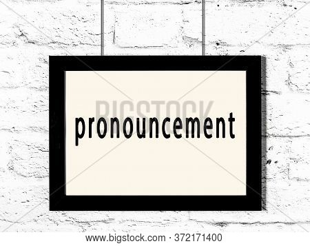 Black Wooden Frame With Inscription Pronouncement Hanging On White Brick Wall
