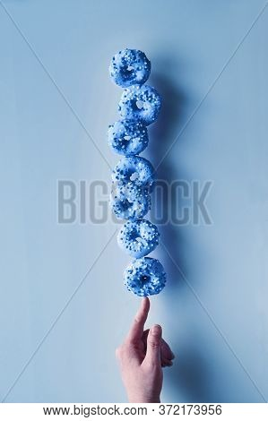 Creative Monochrome Image Toned In Blue Color. Concept Of Perfect Balance. Tower Or Pyramid Of Donut
