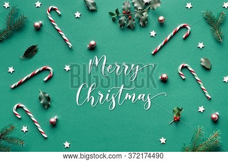 Trendy Geometric Christmas Flat Lay On Green Paper Background With Candy Canes, Holly And Fir Twigs,
