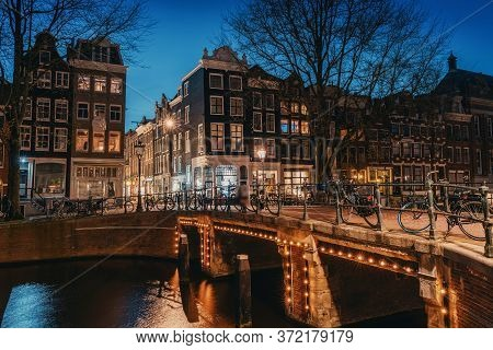 Amsterdam At Night, Bridge Over Water Canal With Evening Lights And Old Houses, Amsterdam, Netherlan