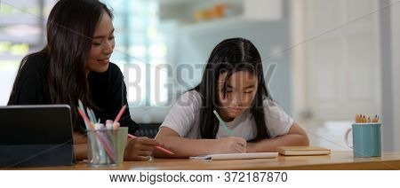 Private Tutor And Student Homeschooling On Wooden Table With Stationery In Living Room