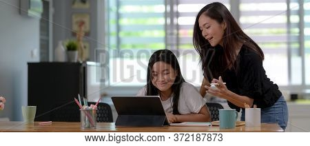 Private Tutor Teaching Her Student With Digital Tablet And Stationery On Wooden Table In Living Room