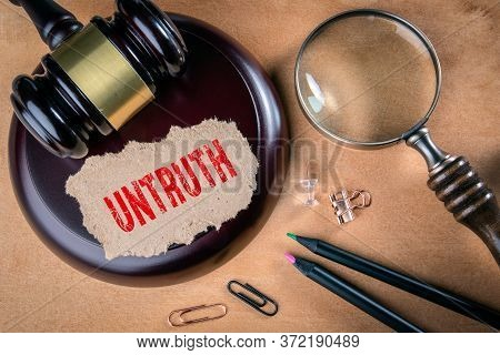 Untruth. Law, Regulations And Judgment Concept. Judges Hammer, Stationery And Magnifying Glass