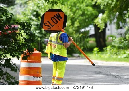 Outdoor Worker Hold Slow Sign At Road Construction Site