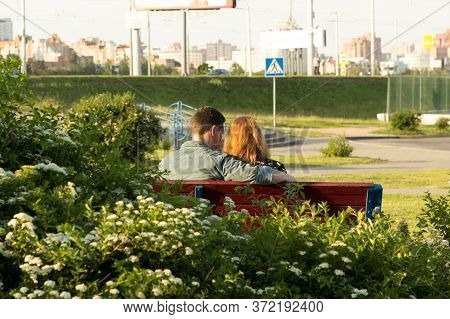 Loving Couple Of Young People, A Girl With Red Hair And A Guy In A Plaid Shirt Are Sitting On A Benc