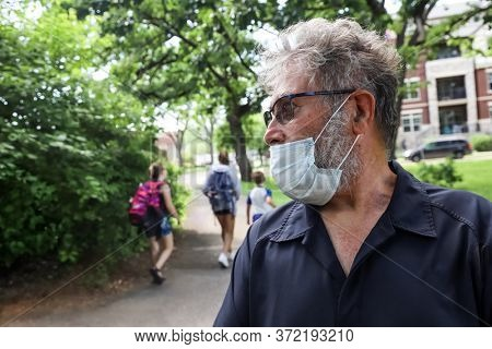 Man wearing face mask incorrectly under his nose outdoors in public