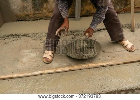 Indian Construction Workers Plastering Floor Using Trowel And Cement Manually, Stock Image.