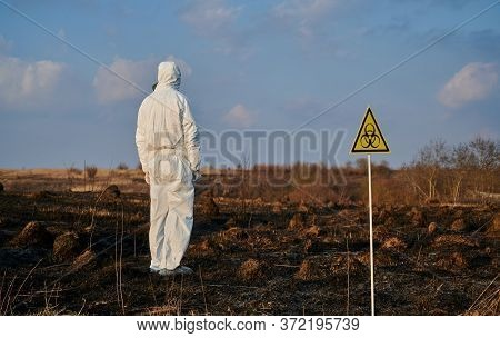 Back View Of Male Environmentalist In Protective Suit Looking At Ashes After Burnt Grass In Field Wi