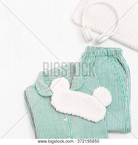 Comfort Neo-mint Color Pajama, Headphones, Fluffy Cushion And Sleeping Eye Mask On White Wooden Back