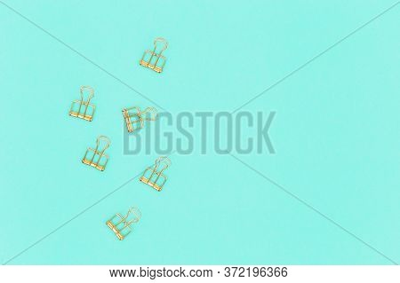 Top View Of Working Table With Golden Colored Metal Clips For Paper And Documents. Background With P