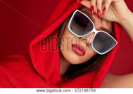 Portrait Of Beautiful Girl With Luxurious Make-up In White Sunglasses And Red Headscarf On Red Backg