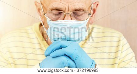 Old Man Wearing Glasses In Disposable Mask Gloves And Yellow Pullover Looks Downward At Home At Coro