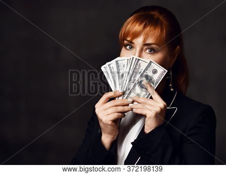 Portrait Of Young Red-haired Business Woman In Black Official Jacket Holding Dollars Cash In Hands I